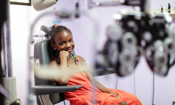 Child smiling in seat in doctor's office