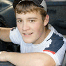 Young man looking at camera from inside of a car