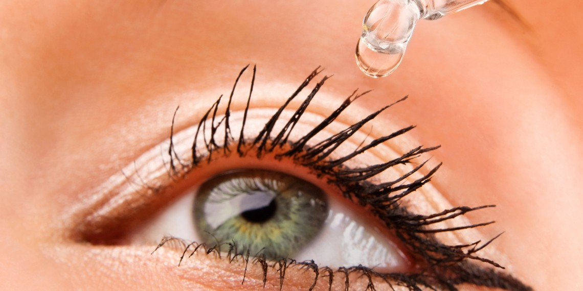 Closeup of eyedropper putting liquid into open eye