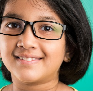 Happy little indian girl smiling while wearing glasses, green ba