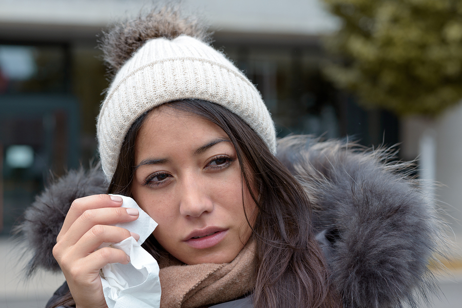 Sad tearful woman in warm winter fashion holding a handkerchief to her face to dry the tears from her eyes looking to the right of the frame with lack lustre eyes and woebegone expression
